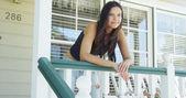 Hispanic woman leaning on rail smiling — Stok fotoğraf