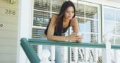 Mixed race woman leaning on rail texting — Stok fotoğraf