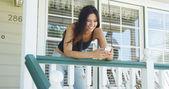 Hispanic woman leaning on rail texting — Stok fotoğraf