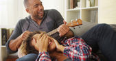 Happy black couple lying on couch with ukulele — Stock Photo