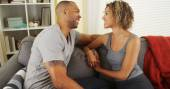 Affectionate black couple talking on couch — Stock Photo