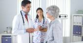 Hispanic doctor talking with elderly patient — Stock Photo
