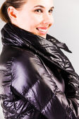 Studio shot of fashionable woman on grey background in fashionable clothes. — Stock Photo