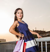 Beautiful young woman with shopping bags on street sunset — Fotografia Stock