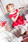 Funny little blonde girl in red dress with pair of new shoes — Stock Photo