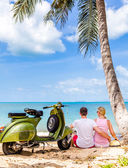 Couple on the beach with retro bike — Stock Photo