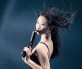 Asian young woman with a gun — Stock Photo