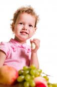 Little Girl Eating Fruit. Isolated on White — Stock Photo