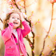 Beautiful baby girl in blooming jasmin tree branches — Stock Photo #57339601