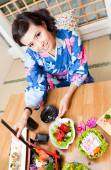 Smiling chinese young woman sitting in a restaurant — Stock Photo