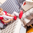 Funny little blonde girl in red dress with pair of new shoes — Stock Photo #57564825