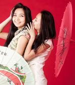 Two cheerful girl-friends. Red background — Stock Photo