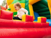 A young girl smiling on inflatable playground — Stockfoto