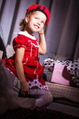 Funny little blonde girl in red dress with new beret — Stock Photo