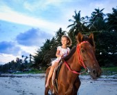 Portrait of an cute little girl riding horses at sunset — Stock Photo