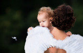 Mother and daughter in the park. Girl plays with white feathers — Stock Photo