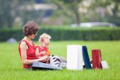 Matka i córka spoczywa na trawnik po zakupy — Zdjęcie stockowe