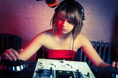 Cool teenage female disc jockey playing music — Stockfoto