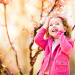 Beautiful baby girl in blooming jasmin tree branches — Stock Photo #58717003