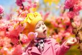 Beautiful baby girl in blooming apricot tree branches — Stock Photo