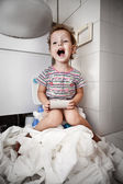 Little girl with a roll of toilet paper — Стоковое фото