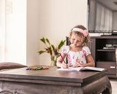 Little girl having fun writing and drawing — Stock Photo