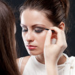 Model during makeup process. Grey background — Stock Photo #59212829