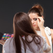 Model during makeup process. Grey background — Stock Photo #59214571