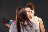 Model during makeup process. Grey background — Stock Photo