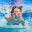 Girl smiles, swimming under water in the pool — Stock Photo #59223617