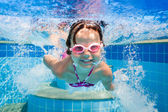 Girl smiles, swimming under water in the pool — Stock Photo