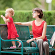 Mother and daughter resting on the lawn after shopping — Stock Photo #59496211