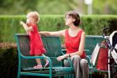 Mother and daughter resting on the lawn after shopping — ストック写真
