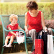 Mother and daughter resting on the lawn after shopping — Stock Photo #59511869