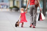 Woman during the shopping with the little girl — Stock Photo