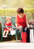Mother and daughter resting on the lawn after shopping — Stock Photo