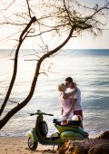 Couple on the beach with retro bike — Stock Photo