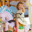 A young girl enjoying a ride on the merry-go-round — Stock Photo #59732667