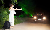 Mom with daughter hitchhiker on the side of road at night — Stock Photo