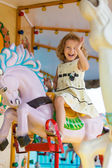 A young girl enjoying a ride on the merry-go-round — Stock Photo