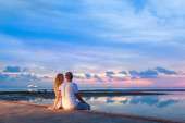 A couple sitting on the beach at sunset — Stock Photo