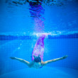 Girl smiles, swimming under water in the pool — Stock Photo #59884571