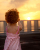 Little girl on a balcony is looking at sunset — Stock Photo