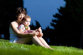 Mother and daughter playing with soap bubbles in the park — Stock Photo