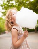 Picture of lovely girl eating cotton candy — Stock Photo