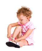 Funny little blonde girl in pink dress with pair of new shoes — Stock Photo