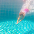 Girl smiles, swimming under water in the pool — Stock Photo #67205189
