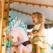 A young girl enjoying a ride on the merry-go-round. — Stock Photo #68053357