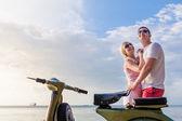 Couple on the beach with retro bike. — Stock Photo