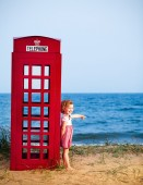 Portrait of a little girl standing near public telephone booth. — Stock Photo